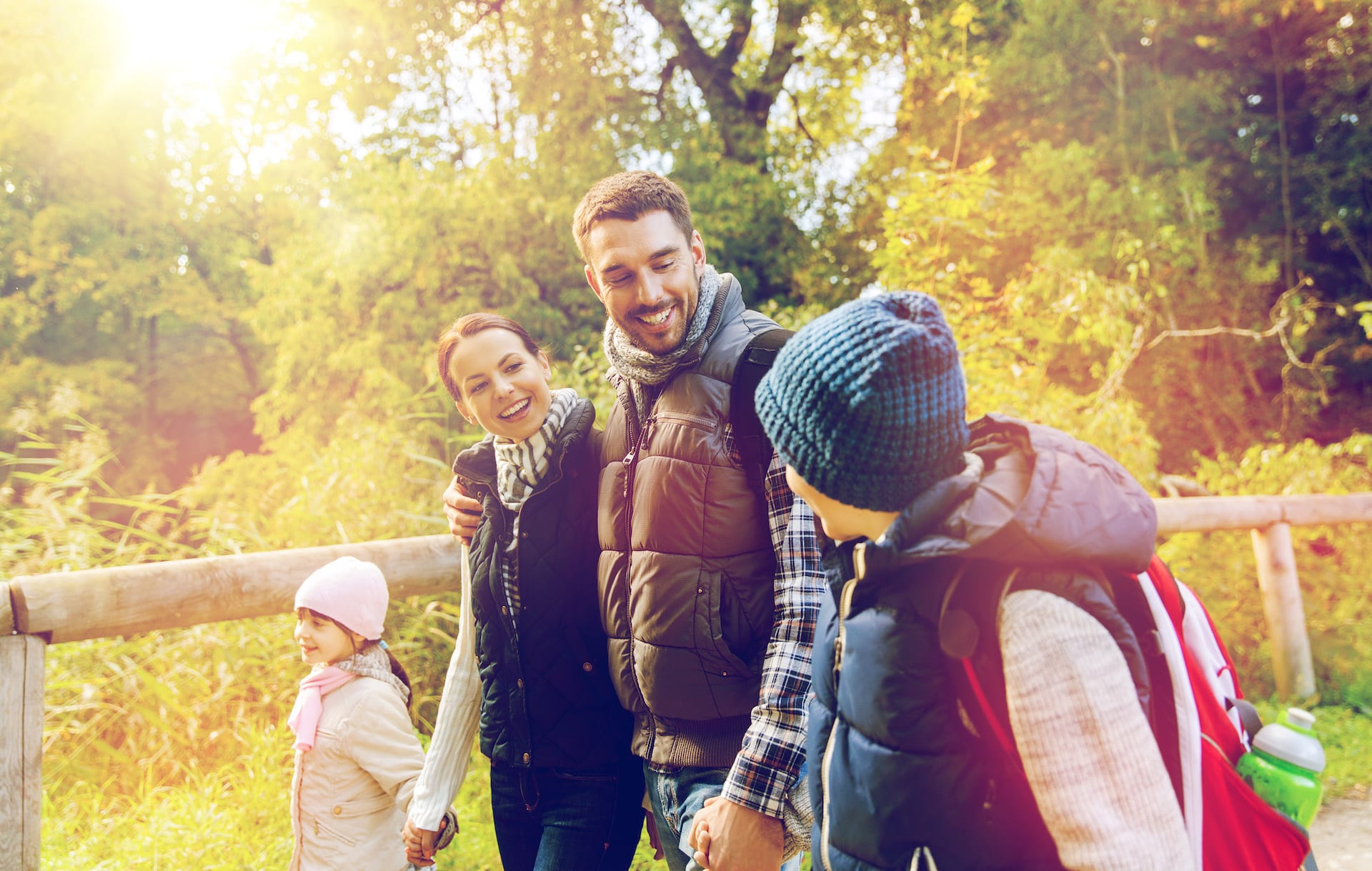 travel, tourism, hike and people concept - happy family with backpacks hiking in woods